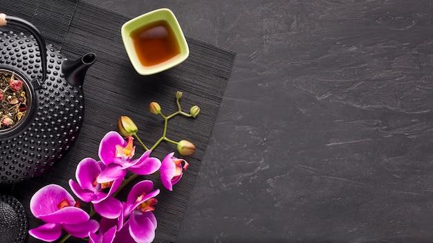 Kräutertee und schöne orchideenblume auf schwarzer platzmatte über schiefersteinhintergrund Kostenlose Fotos