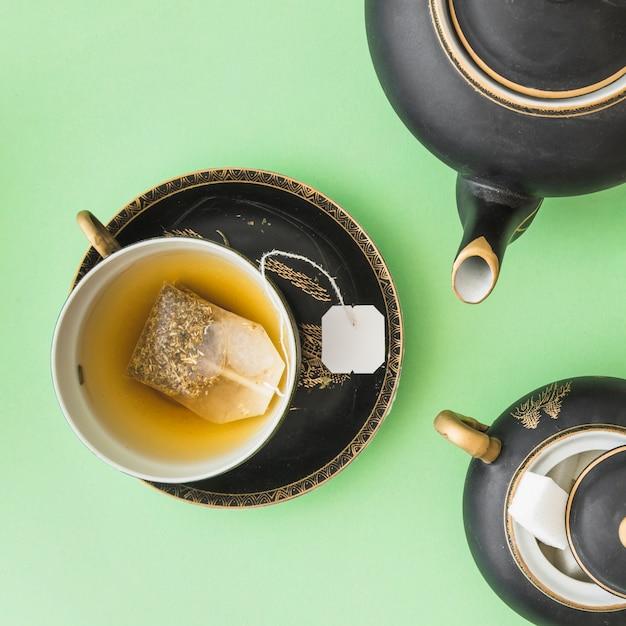 Kräuterteebeutel in der schale mit teekannen- und zuckerwürfeln auf grünem hintergrund Kostenlose Fotos