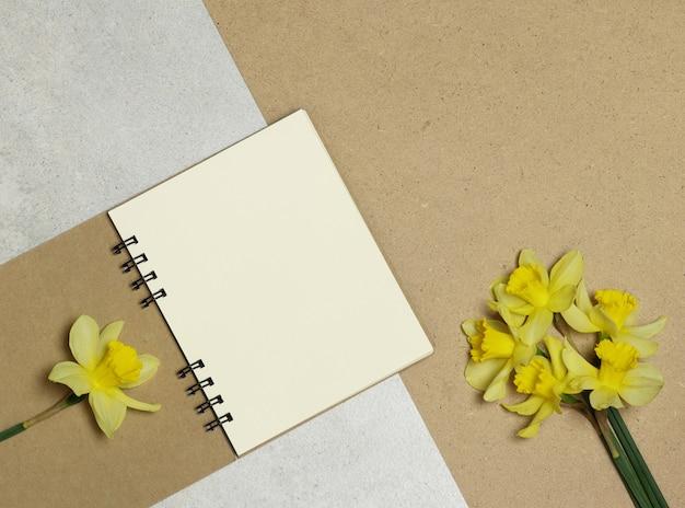 Kraftpapieranmerkungen, gelbe blumen auf stein und holztisch Premium Fotos