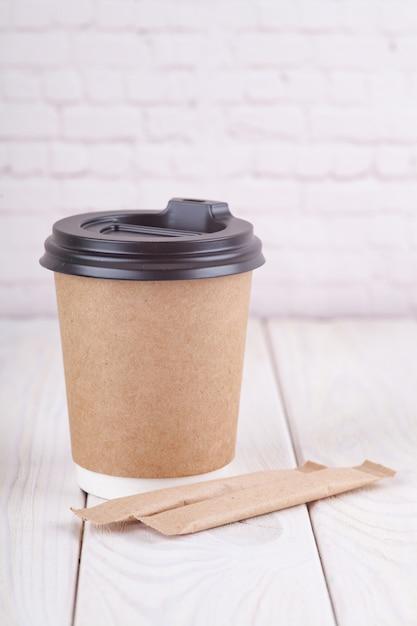 Kraftpapierkaffeetassen auf einer weißen tabelle nahe hellem wandhintergrund Premium Fotos