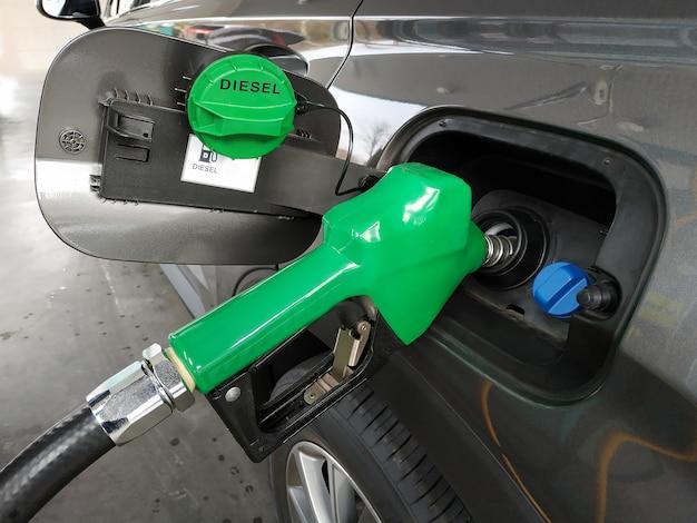 Kraftstoffdüsen, die dieselkraftstoff im auto an einer pumpentankstelle hinzufügen. Premium Fotos