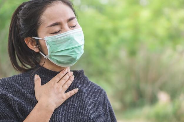 Kranke asiatische frau mit maske mit erkältung und grippe Premium Fotos