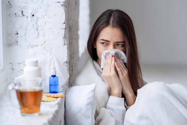 Kranke frau erkältet, sich krank fühlend und beim papiertuch niesend Premium Fotos