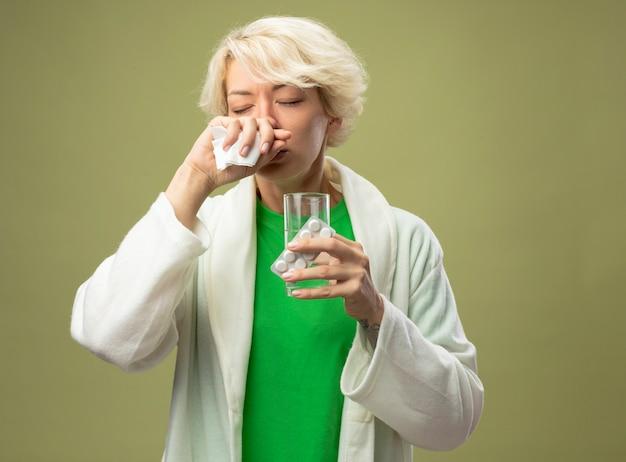 Kranke frau mit kurzen haaren, die sich unwohl fühlen, halten glas wasser und blase mit pillen, die ihre nase mit serviette abwischen, die über hellem hintergrund steht Kostenlose Fotos