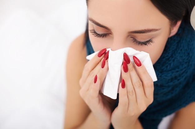 Kranke frau und grippe. frau kalt erwischt. niesen in das gewebe Premium Fotos