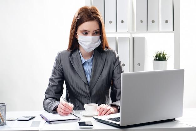 Kranke geschäftsfrau in einer medizinischen schutzmaske im büro Premium Fotos