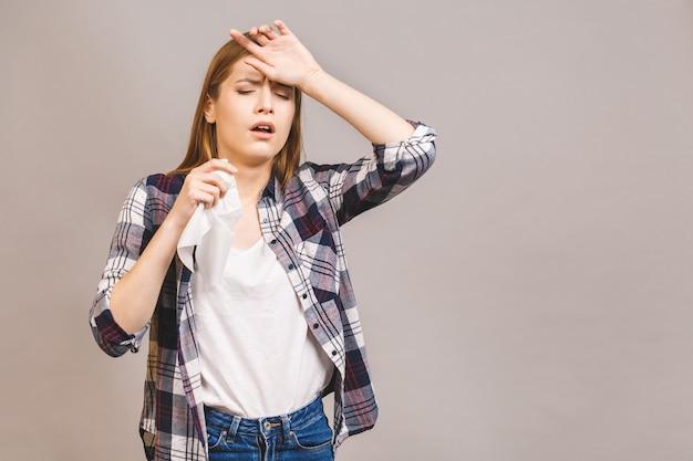 Kranke junge blonde frau in lässig mit halsschmerzen, hand auf ihrem kopf haltend. halsschmerzen, schmerzhaftes schluckkonzept Premium Fotos