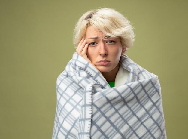 Kranke ungesunde frau mit kurzen haaren, die sich unwohl fühlen, eingewickelt in eine decke, die an grippe leidet und ihren kopf berührt, der über der hellen wand steht Kostenlose Fotos