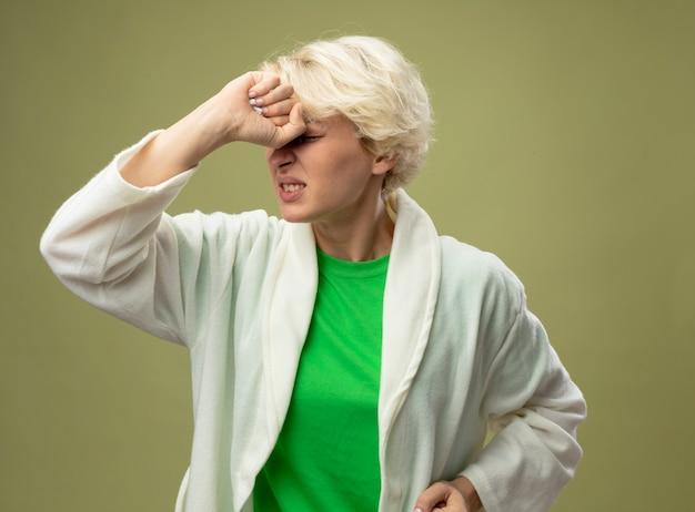 Kranke ungesunde frau mit kurzen haaren, die sich unwohl fühlen, wenn sie verärgert sind und ihre stirn berühren, die über hellem hintergrund steht Kostenlose Fotos