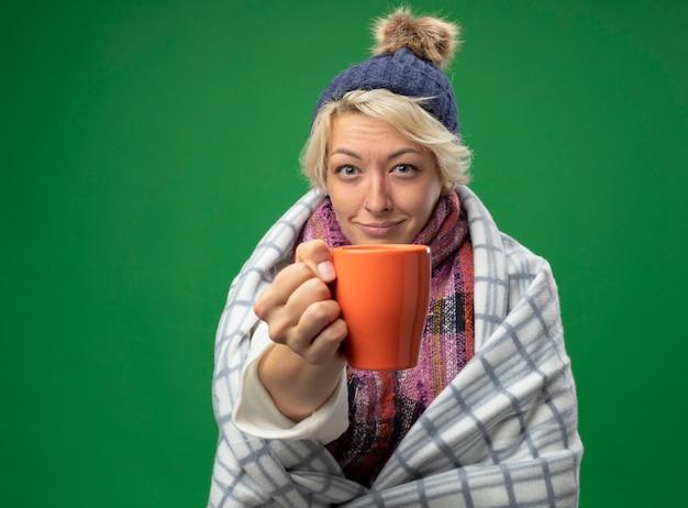 Kranke ungesunde frau mit kurzen haaren in warmem schal und hut, die sich besser in decke gewickelt fühlen, die tasse tee lächelnd über grünem hintergrund stehend hält Kostenlose Fotos