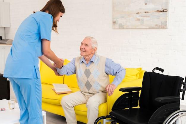 Krankenschwester, die altem mann hilft aufzustehen Kostenlose Fotos
