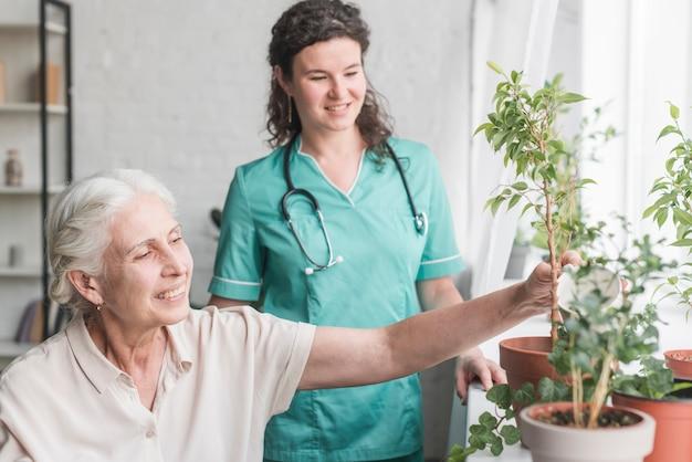 Krankenschwester, die den älteren patienten betrachtet, der die anlage wässert Kostenlose Fotos