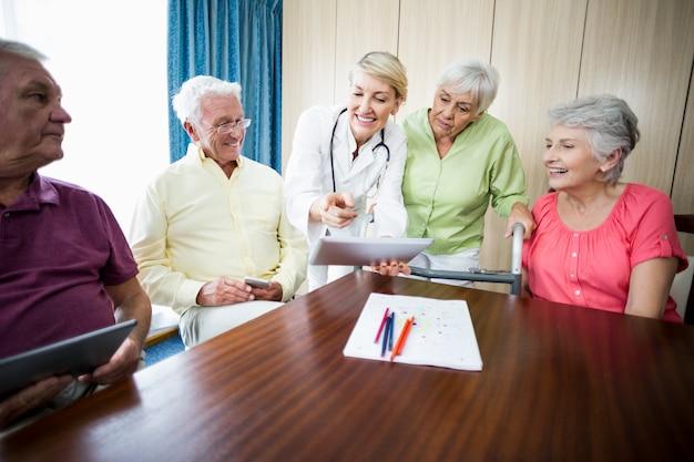 Krankenschwester, die senioren etwas zeigt Premium Fotos