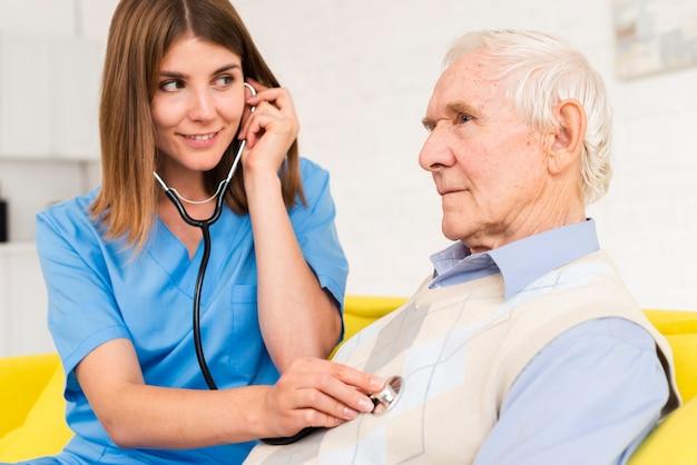 Krankenschwester, die stethoskop auf altem mann verwendet Kostenlose Fotos