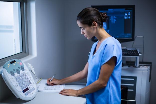 Krankenschwester macht sich notizen im röntgenraum Kostenlose Fotos