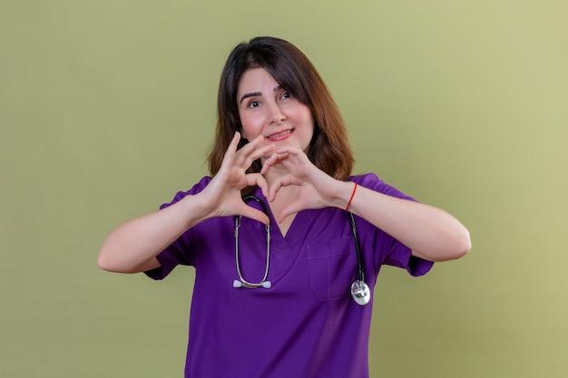 Krankenschwester mittleren alters, die uniform trägt und mit stethoskop macht romantische herzgeste über brust, mit lächeln auf gesicht über isolierter grüner wand Kostenlose Fotos
