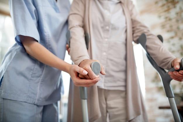 Krankenschwester trägt uniform unterstützende frau mit krücken Premium Fotos