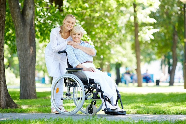 Krankenschwester umarmt ältere frau im rollstuhl Kostenlose Fotos