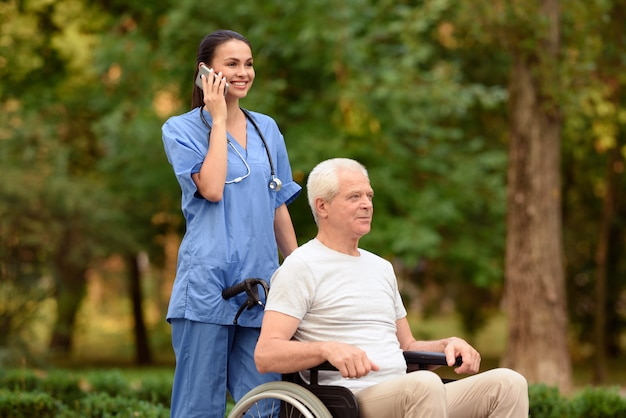 Krankenschwester und alter mann, die in einem rollstuhl im park sitzen. Premium Fotos