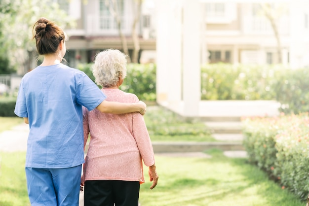 Krankenschwestersorgfaltunterstützung, die mit der älteren frau im freien geht Premium Fotos
