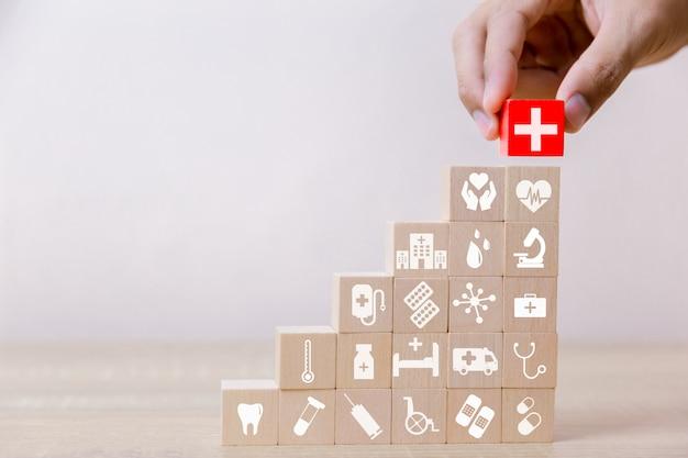 Krankenversicherungs-konzept, hand, die den hölzernen block stapelt mit dem ikonengesundheitswesen medizinisch, für gesundheit vereinbart Premium Fotos
