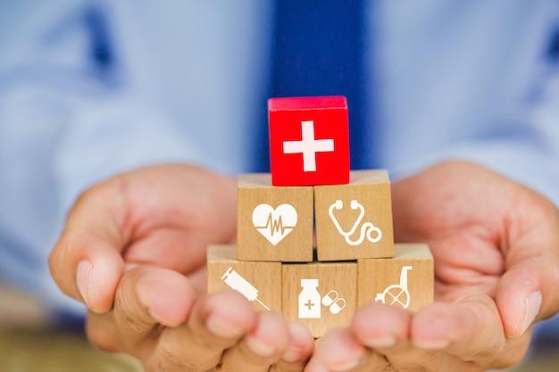 Krankenversicherungs-konzept, hand, die den hölzernen block stapelt mit dem ikonengesundheitswesen medizinisch vereinbart Premium Fotos