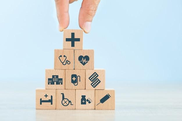 Krankenversicherungs-konzept, hand, die den hölzernen block stapelt mit dem ikonengesundheitswesen medizinisch vereinbart. Premium Fotos