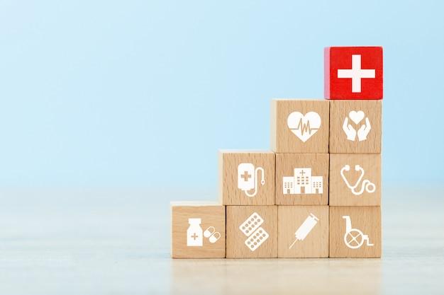 Krankenversicherungs-konzept, hölzernen block vereinbarend, der mit dem ikonengesundheitswesen stapelt, das medizinisch ist. Premium Fotos