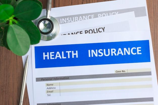Krankenversicherungsformular mit stethoskop in der draufsicht Premium Fotos