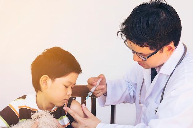 Kranker asiatischer junge, der vom männlichen doktor behandelt wird Kostenlose Fotos