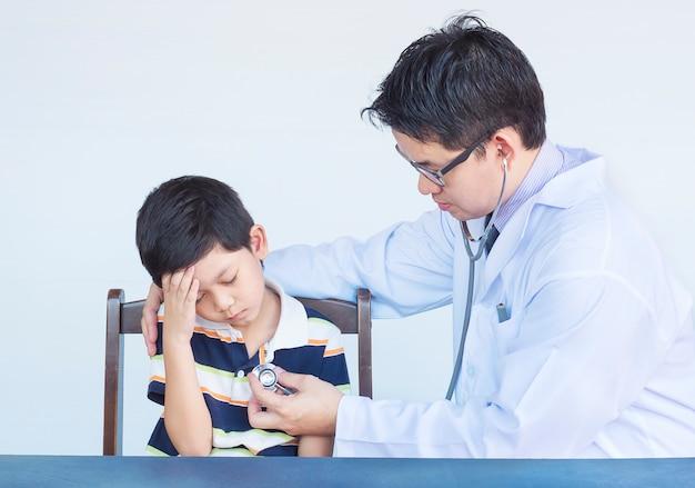Kranker asiatischer junge, der vom männlichen doktor über weißem hintergrund überprüft wird Kostenlose Fotos