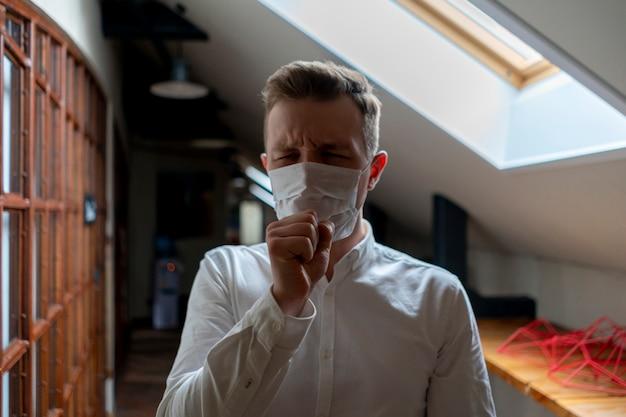 Kranker geschäftsmann in seiner schutzmaske der büroabnutzung. krankheitskonzept Premium Fotos