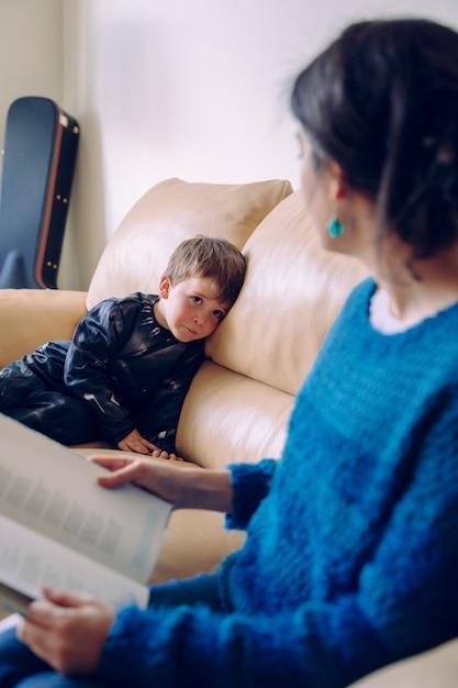 Kranker kleiner junge, der eine geschichte aus einem buch hört. lebensstil mit kindern im haus. kleines kind zu hause geerdet. junge mutter liest ihrem kind die hausaufgaben ohne schulzeit vor. Premium Fotos