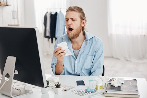 Kranker männlicher büroangestellter hält taschentuch, niest, hat unglücklichen und müden ausdruck, isoliert vor bürohintergrund. ungesunder junger mann verbreitet bakterien Kostenlose Fotos