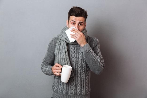 Kranker mann in der strickjacke und in schal, die laufende nase beim halten der tasse tee und schauen haben Kostenlose Fotos