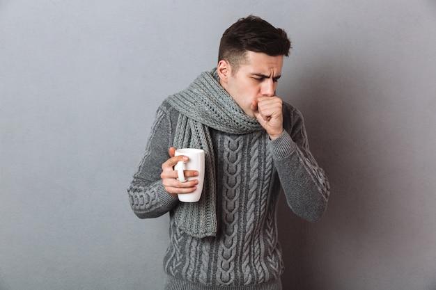 Kranker mann in der strickjacke und in schal, die tasse tee beim haben des hustens halten Kostenlose Fotos