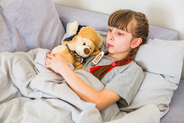 Krankes mädchen mit thermometer Kostenlose Fotos