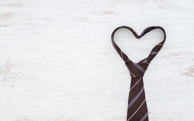 Krawatte in der herzform auf weißem holztischhintergrund des schmutzes. Premium Fotos
