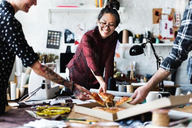 Kreative, die spaß haben und pizza essen Premium Fotos