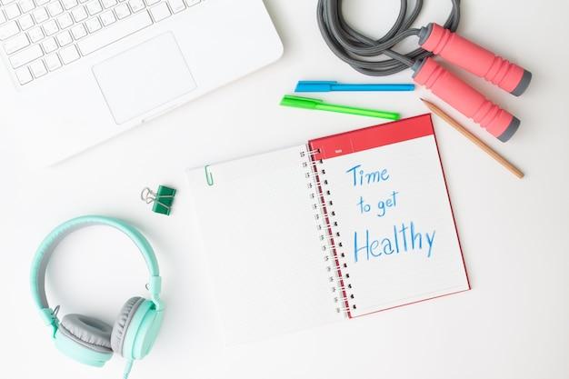 Kreative flache lage des arbeitsplatzes schreibtisch mit laptop, kopfhörer und training Premium Fotos