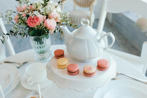 Kreative frühlingszusammensetzung. elegante süßspeise macarons, tasse tee oder kaffee und schöner pastell färbten beige und lebende korallenblumenblumenstrauß auf weißem marmor Premium Fotos