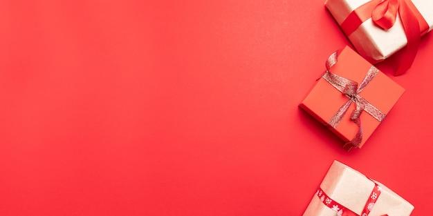 Kreative geschenk- oder geschenkkästen mit goldbögen und sternkonfettis auf roter draufsicht. flache laienzusammensetzung für geburtstag, weihnachten oder hochzeit. Premium Fotos