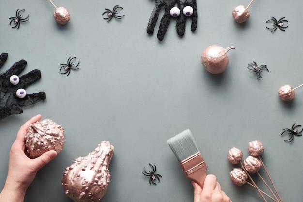 Kreative halloween-wohnung lag auf grauem papier mit kopierraum. rahmen aus rosa vergoldeten kürbissen, schwarzen netzhandschuhen mit schokoladenaugen, hand mit pinsel und einigen schwarzen spinnen. Premium Fotos