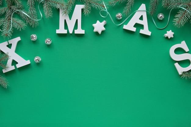 Kreative weihnachtswohnung lag mit großen weißen buchstaben weihnachten auf grünem textil, kopierraum. tannenzweige mit sternen verziert, spiegel discokugeln. Premium Fotos