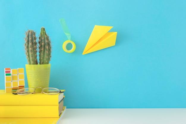 Kreativer arbeitsplatz in den blauen und gelben farben mit kaktus Kostenlose Fotos
