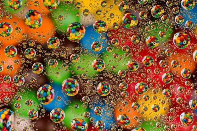 Kreativer bunter hintergrund. bunte süßigkeit durch wassertropfen auf glas Premium Fotos