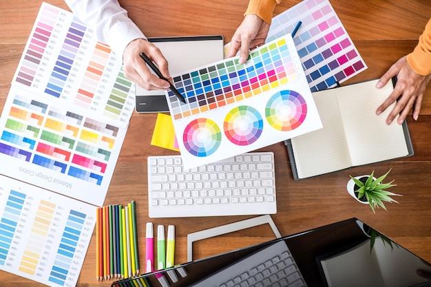 Kreativer grafikdesigner mit zwei kollegen, der an farbauswahl und farbmustern arbeitet und zeichnen auf grafiktablette Premium Fotos