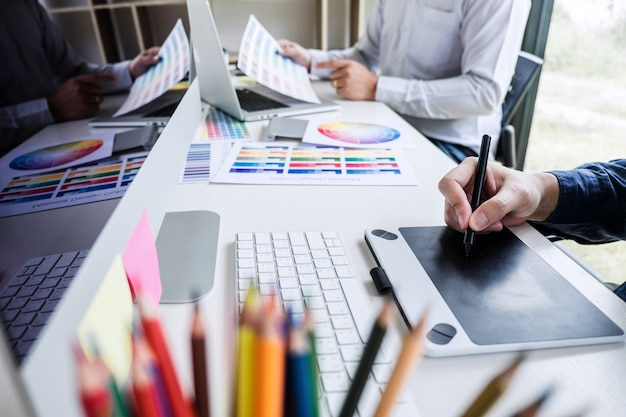 Kreativer grafikdesigner mit zwei kollegen, der an farbauswahl und farbmustern arbeitet Premium Fotos