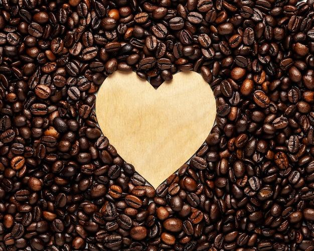 Kreativer hintergrund aus holzherz mit kaffeebohnen. Premium Fotos