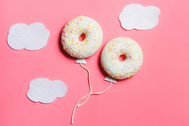 Kreativer lebensmittel-minimalismus, donut in form des ballons im himmel mit wolkenhintergrund Premium Fotos